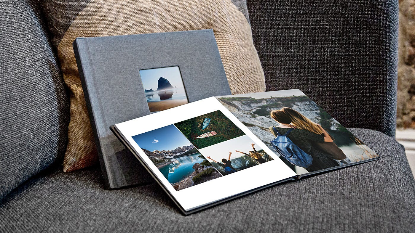 Year in review style book from Printique, propped against a pillow on a couch.