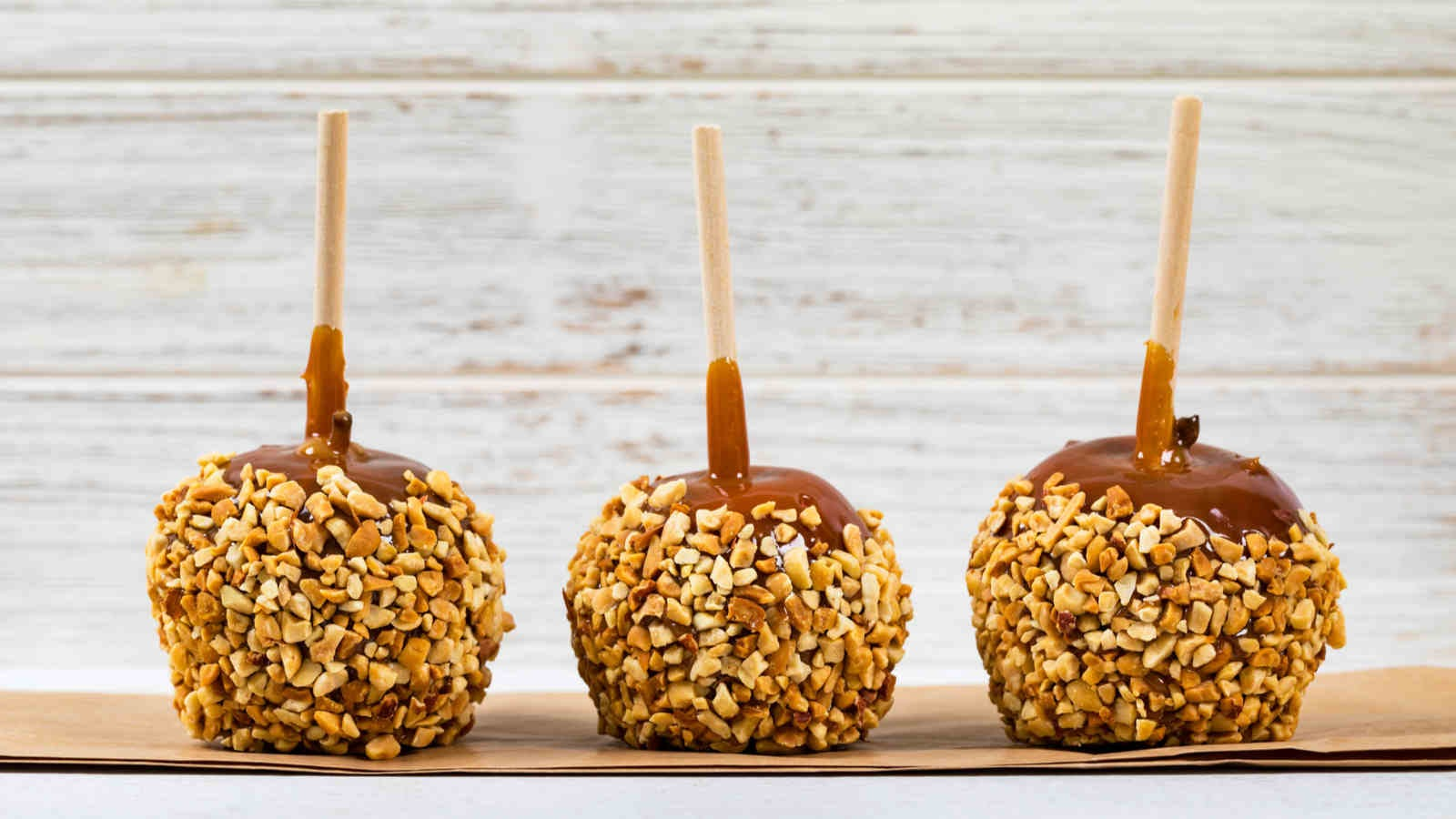 Three caramel apples dipped in chopped nuts, sitting upside-down on a table.
