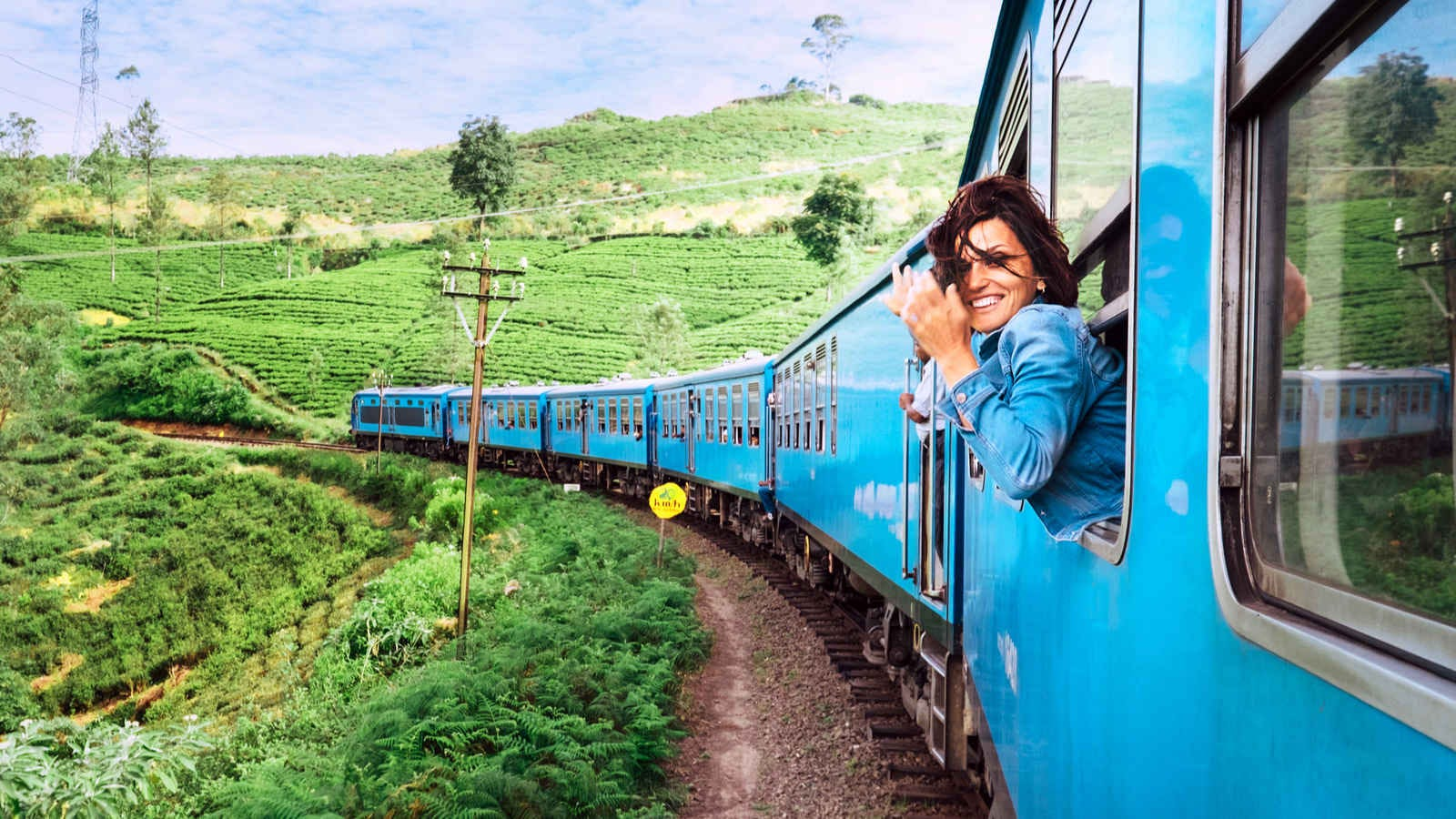 woman leaning out the window of a train, smiling
