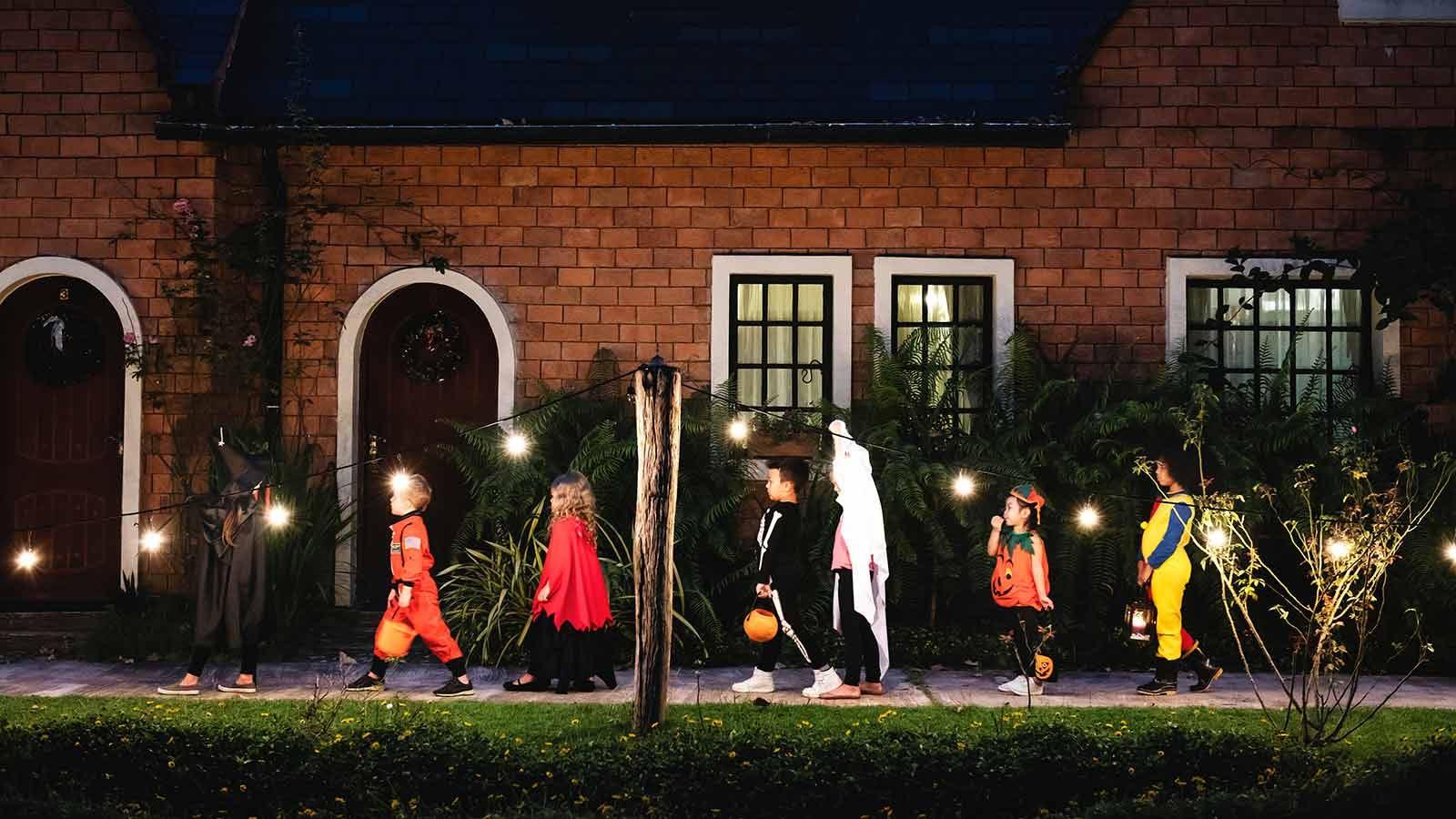 kids walking down a sidewalk lined with lights