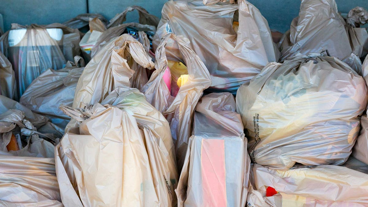 A car trunk full of groceries wrapped up in plastic bags.