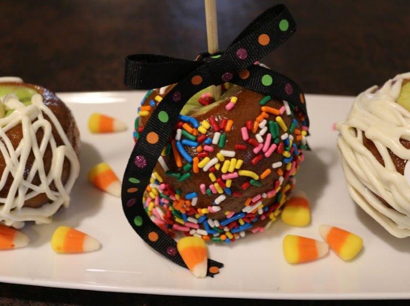 A caramel apple coated with rainbow sprinkles
