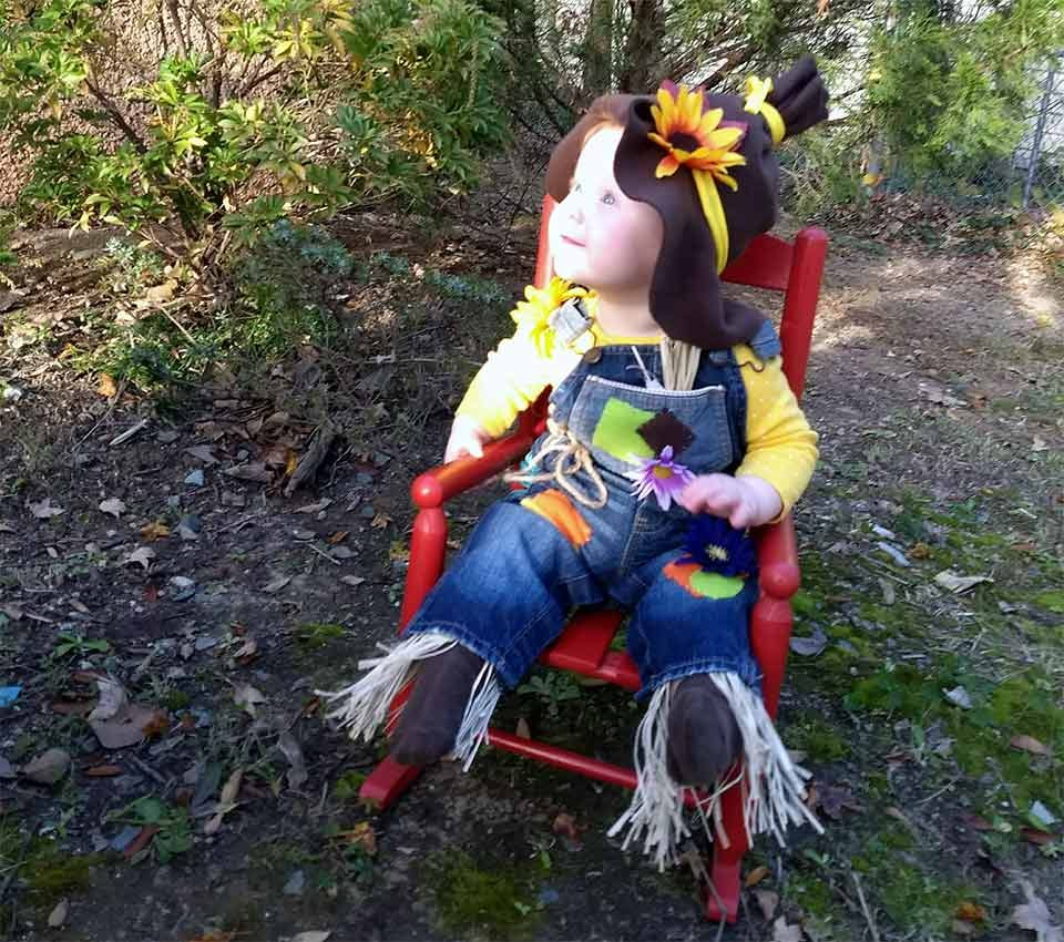 young girl dressed up as an adorable scarecrow