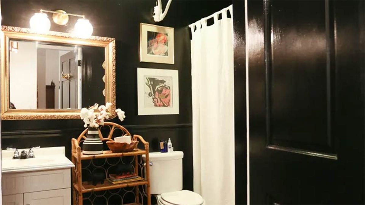 A small windowless bathroom given a very chic coat of shiny black paint