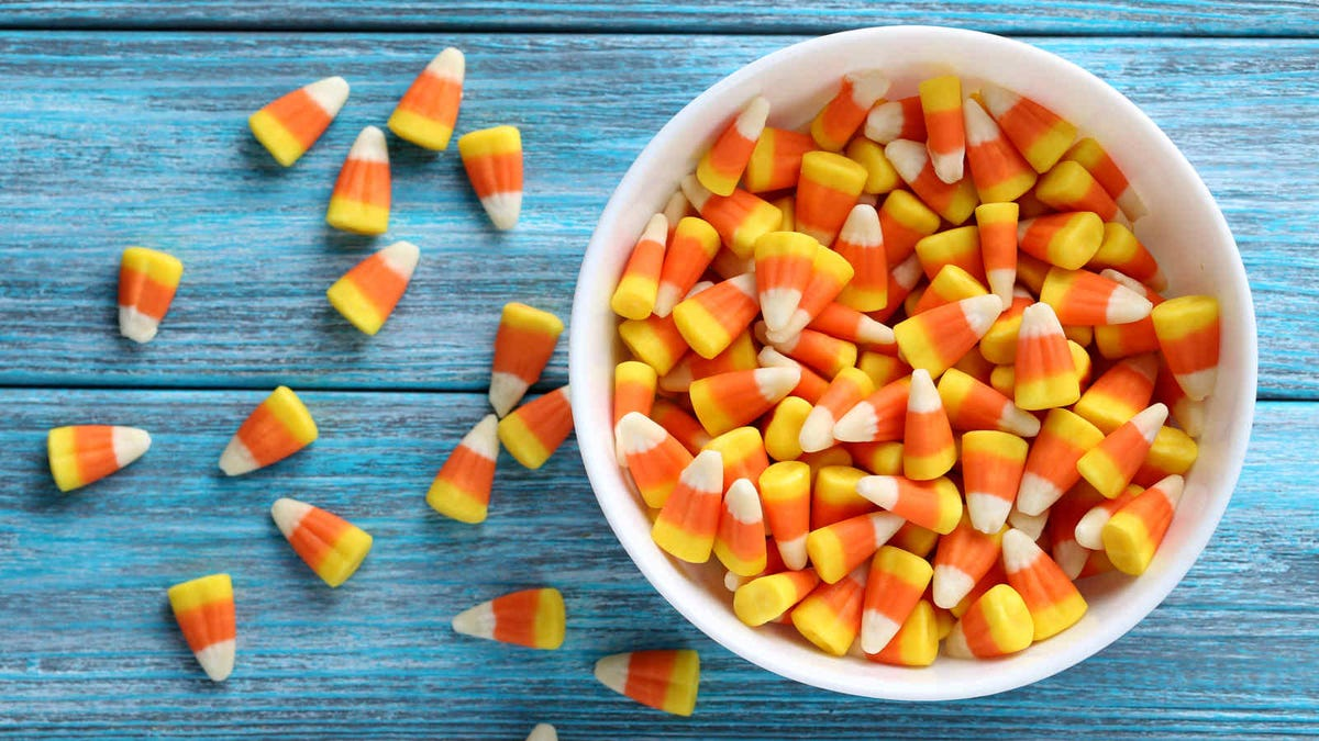 A bowl of candy corn on a turquoise wooden table.