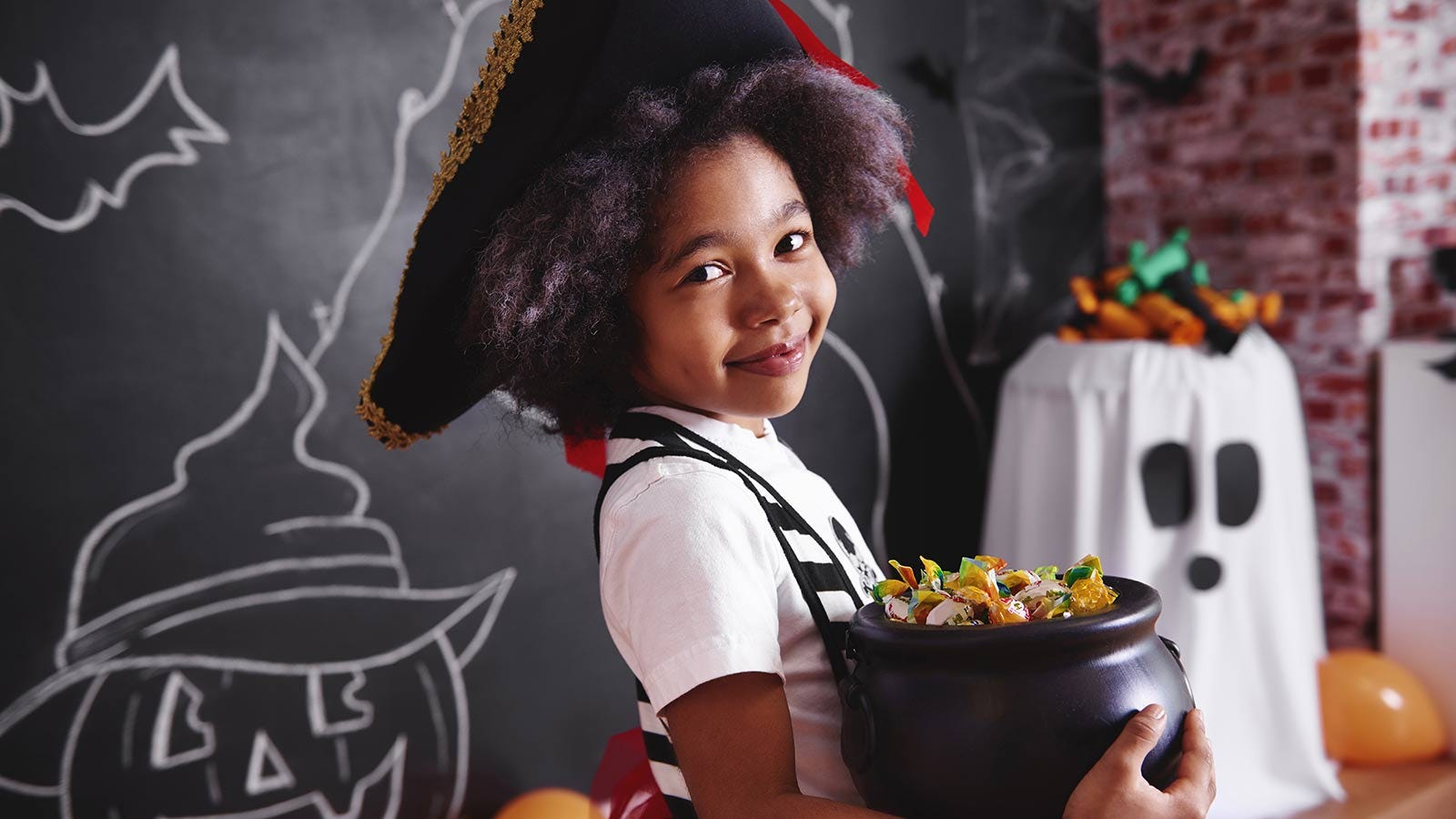 little girl holding a bucket of candy to hand out on Halloween