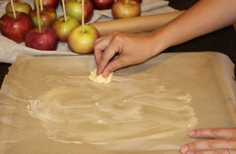 Generously buttering the parchment paper (apples in the background)