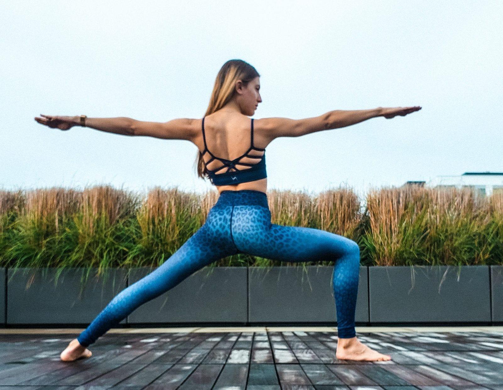 Woman doing a warrior II pose in blue leopard leggings