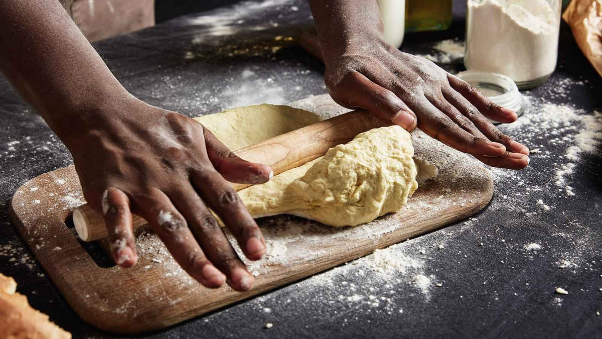 man rolling out bread dough to prepare Thanksgiving sides ahead of schedule