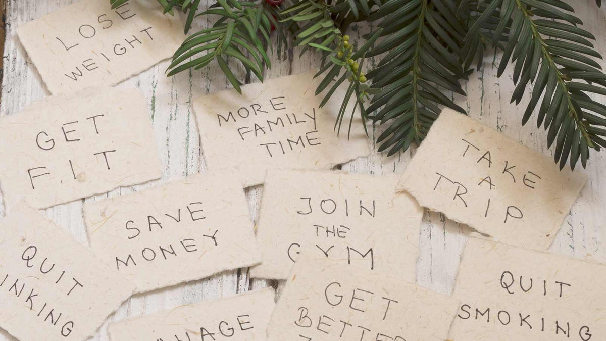 cards with New Year's Resolutions written out on them, sitting on a table by a pine branch