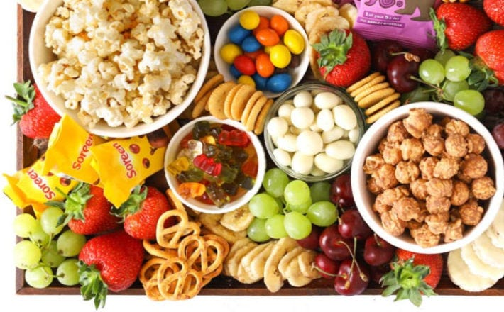 A snack platter filled with popcorn, various candies, fresh fruit, and pretzels.