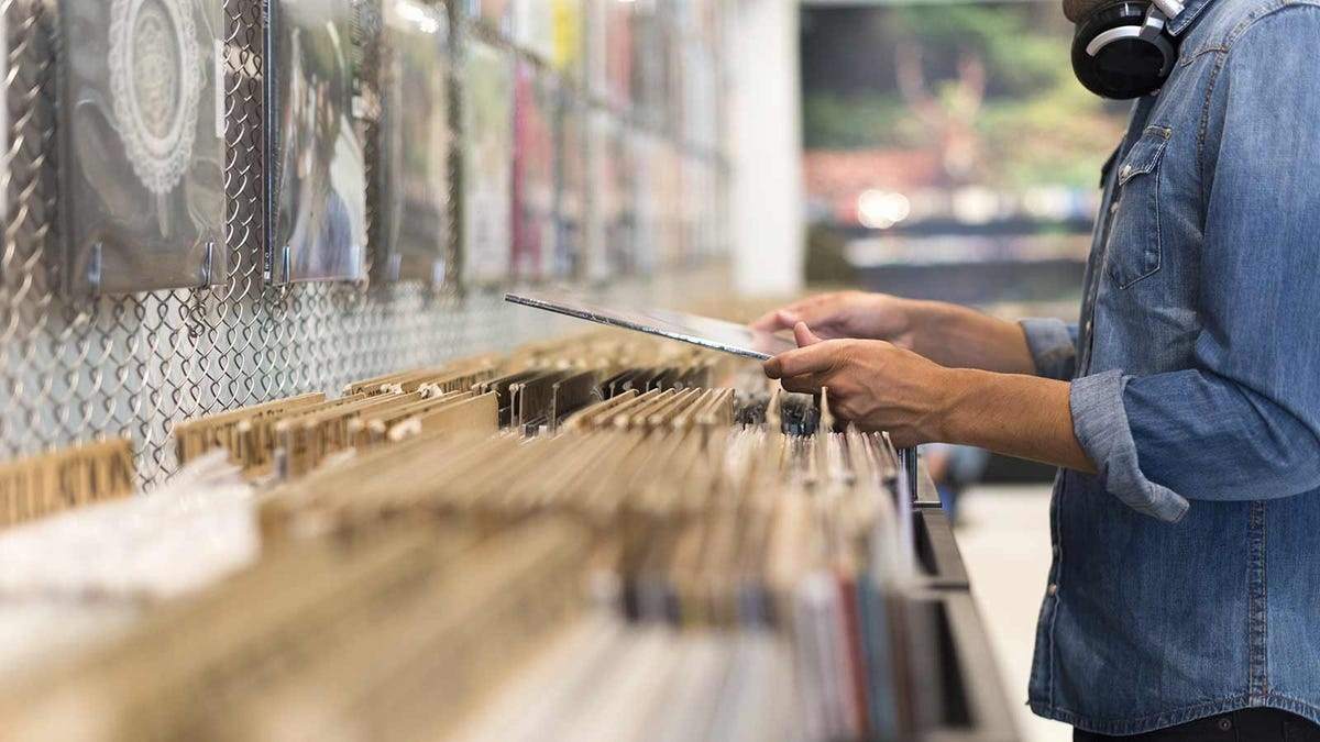 man looking at records in a record shop