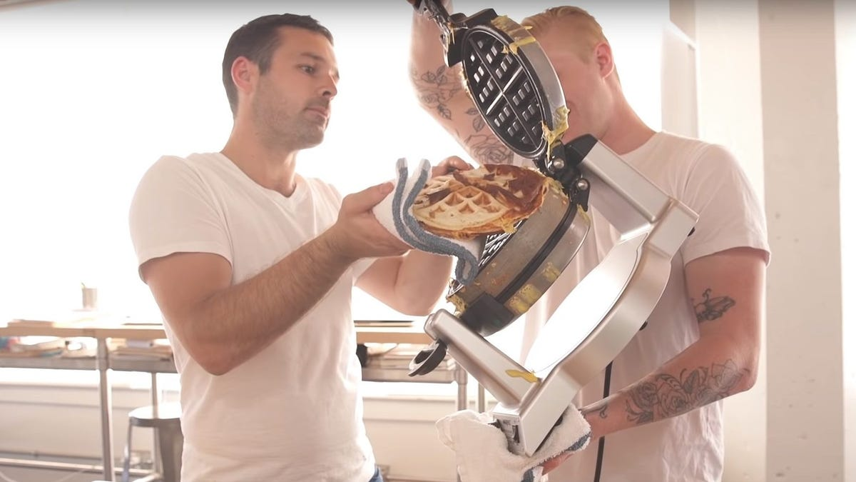 two chefs work to remove a waffle iron fajita from a Waring waffle iron