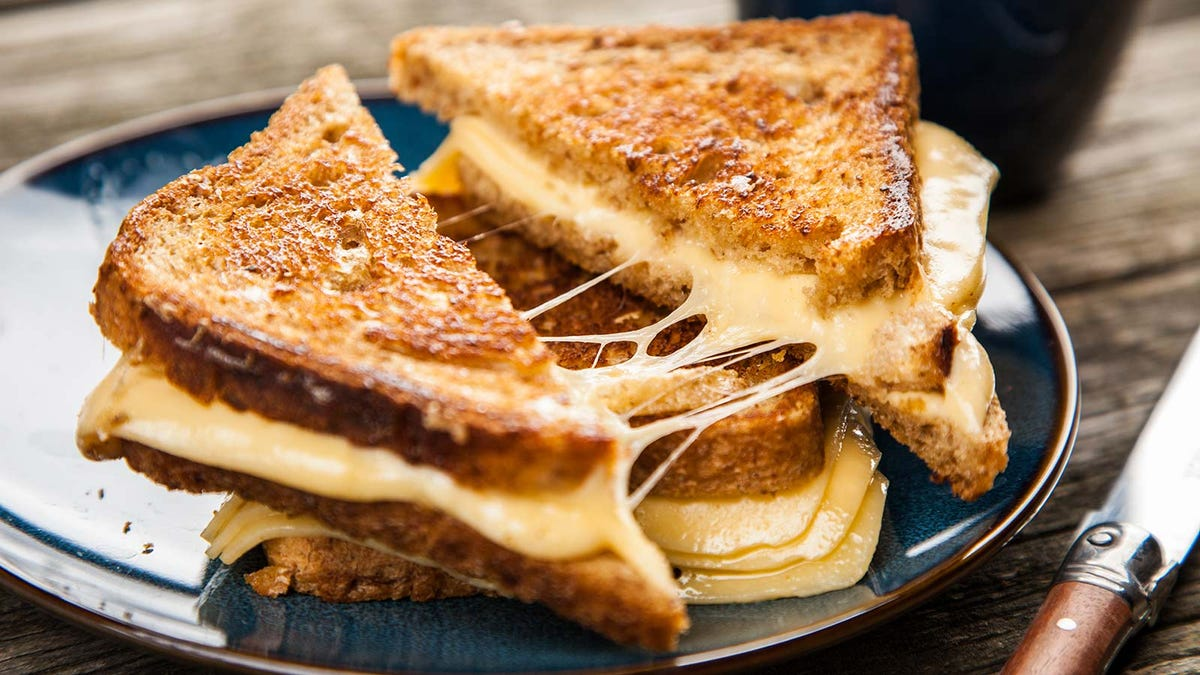 A plate of grilled cheese sandwiches, sliced in halves.