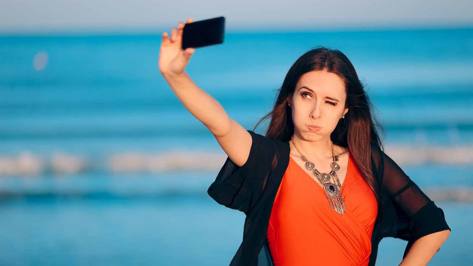 A woman on a beach taking a selfie with her phone.