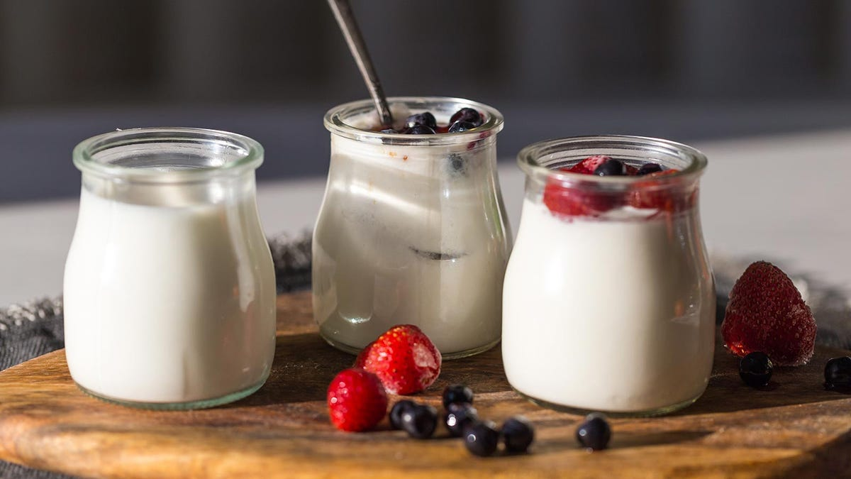 Yogurt in small glass jars on a cutting board, surrounded by berries.