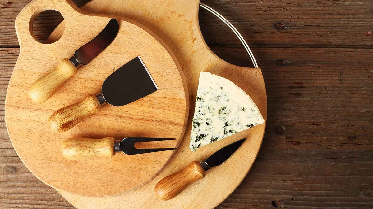 Two cutting boards with a a block of cheese and a set of specialty cheese knives sitting on them.
