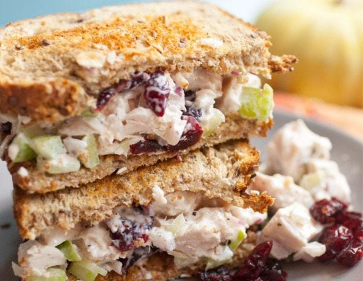 A turkey salad sandwich, cut in half with one side stacked on top of the other.