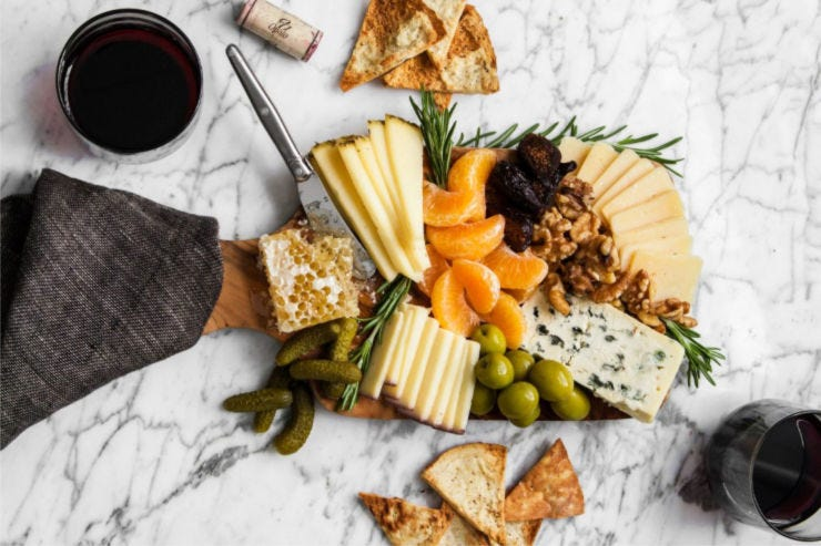 A small winter cheese board filled with rosemary garnish, sliced clementine, pickles, olives and honey comb.