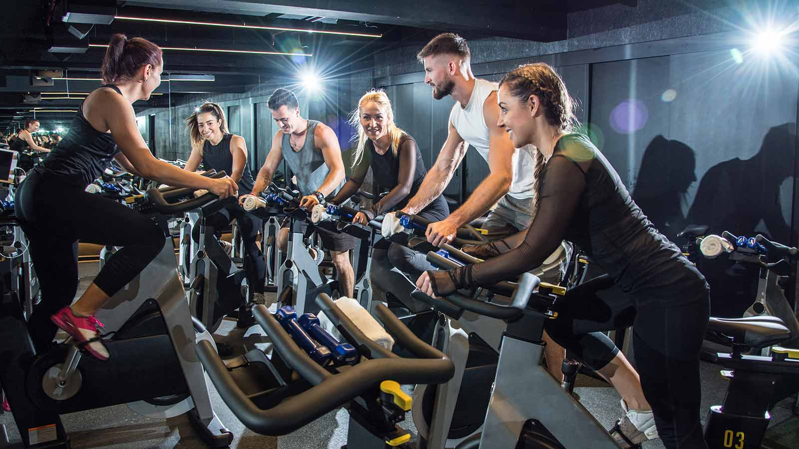 group of men and women in a cycling class following their instructors guidance