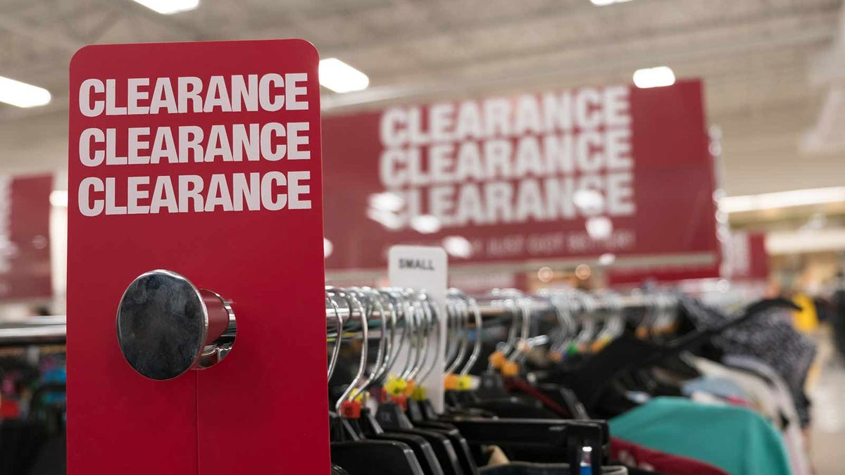 bright red clearance sign marking a rack of discounted clothing