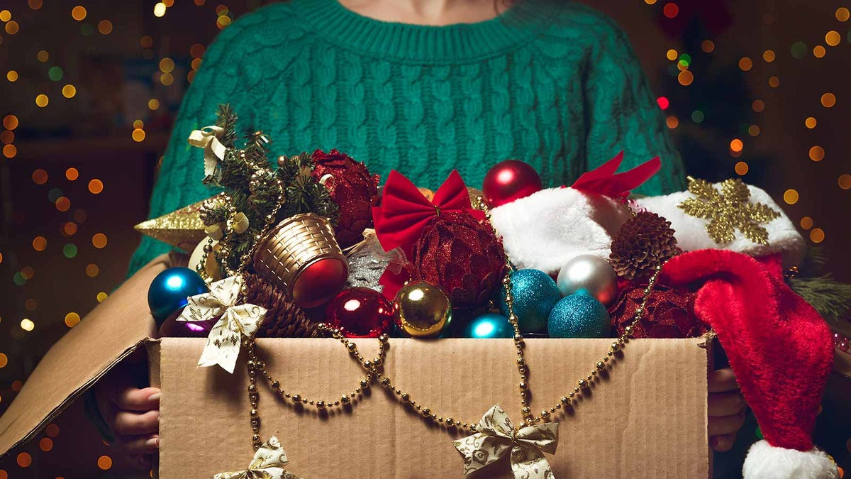 woman holding a big cluttered box of holiday decorations