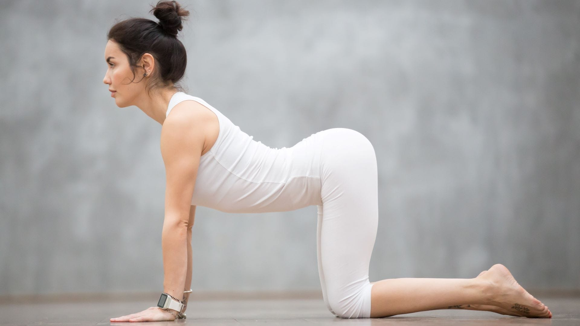 A woman in a Yoga Cat Pose.