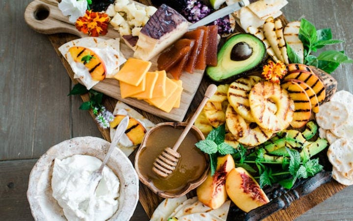 A cheese snack board filled with char grilled pineapples, and apples along with fresh honey, various cheeses and fresh avocado.