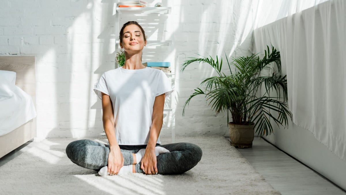 A woman in a seated yoga pose in a bedroom.