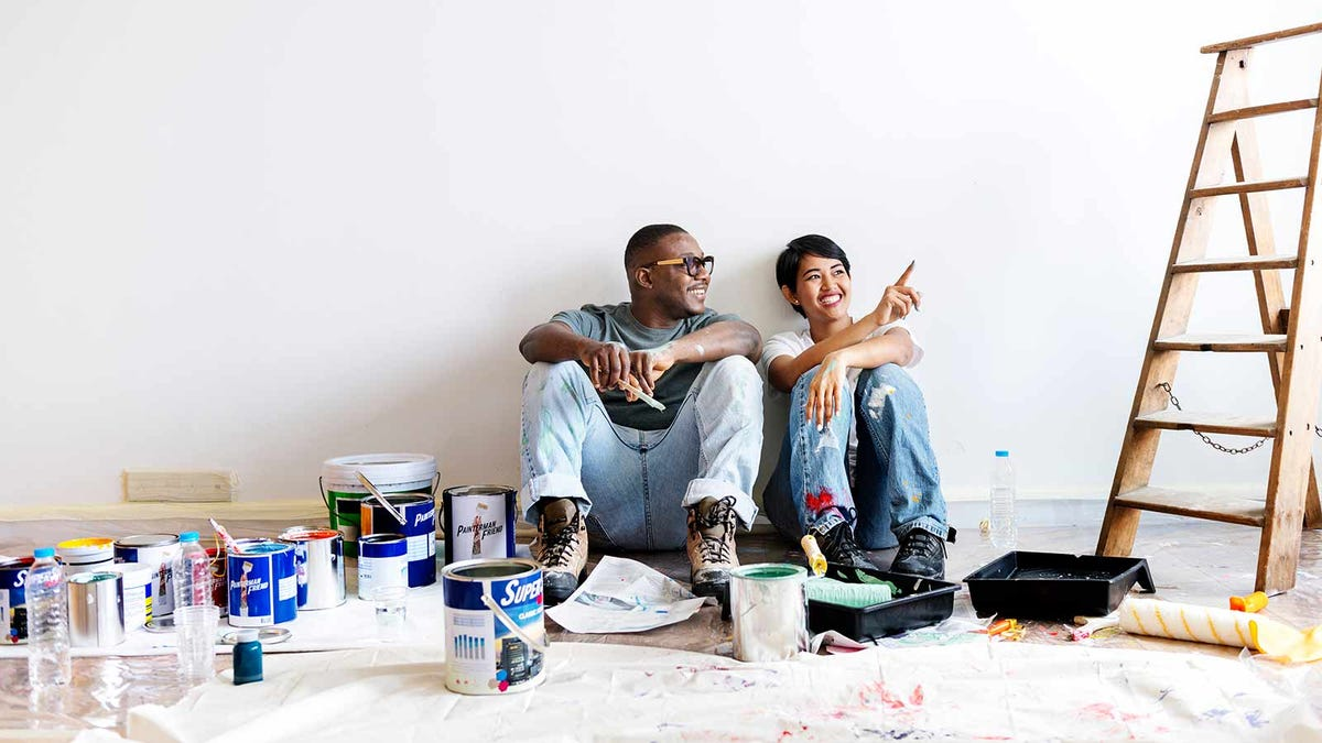 two people taking a break from painting a room