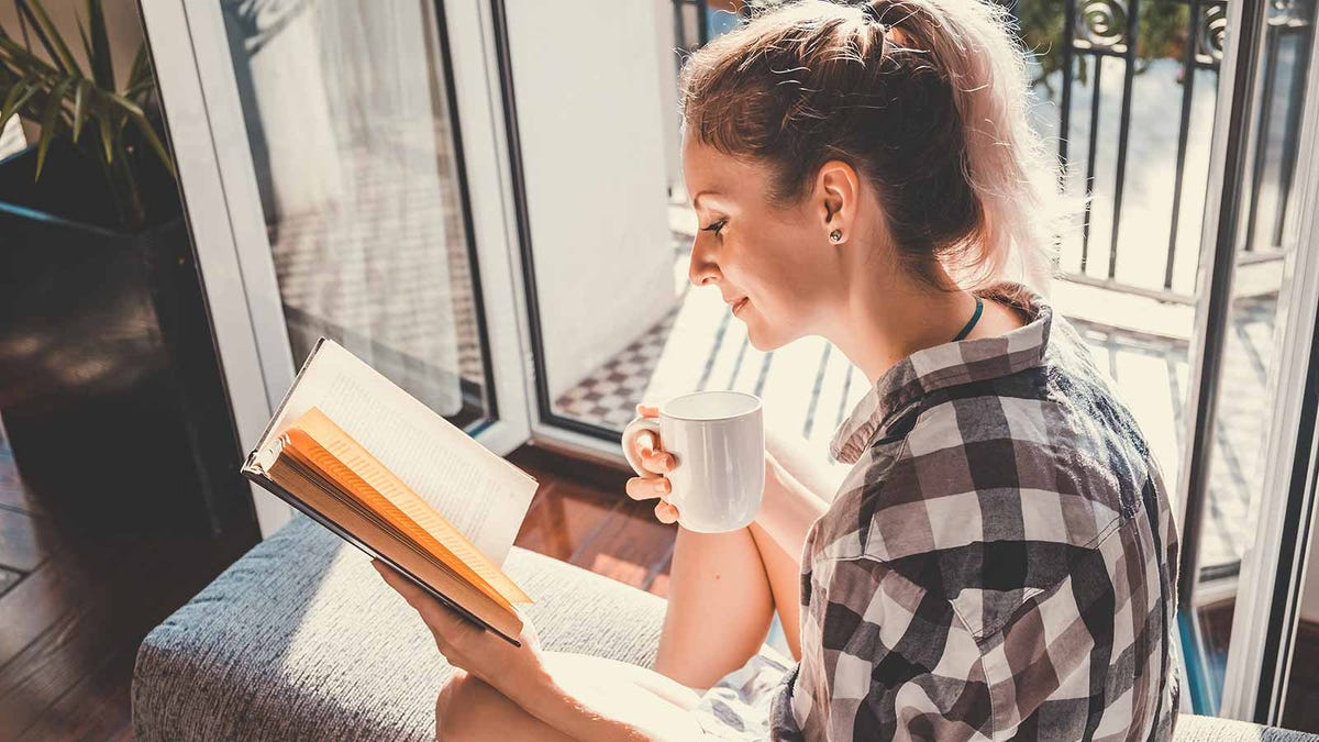 A woman sitting on a window seat reading a book and holding a coffee mug.