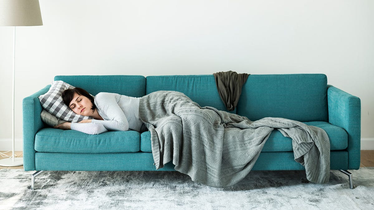 Woman napping on a long modern couch in a brightly lit living room.