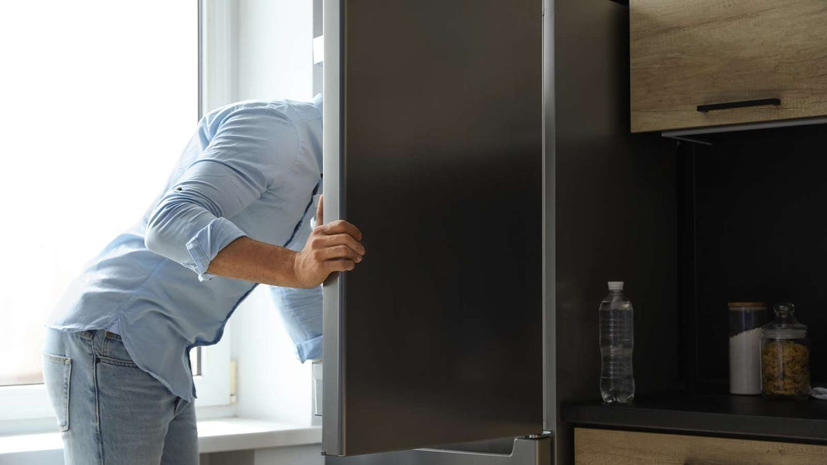 A man looking in a refrigerator, is head obscured by the door.