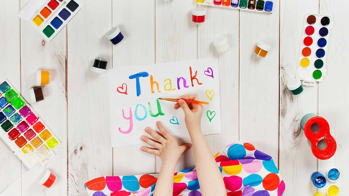 child painting a thank you note with craft supplies