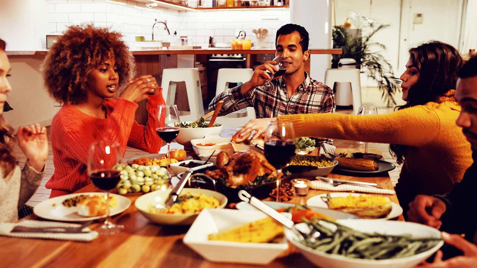 A group of people eating a meal at a kitchen table.