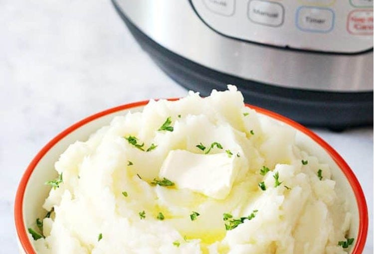 A bowl of mashed potatoes with an Instant Pot in the background.