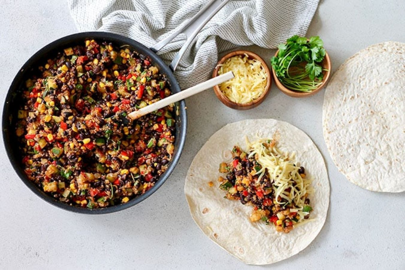 A tortilla on a counter with the black bean and quinoa filling spread in the middle, next to a large bowl full of it.