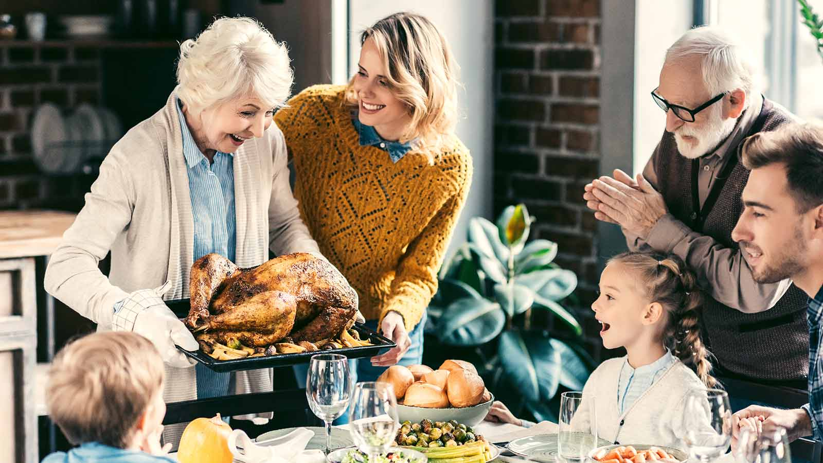 family gathered around a holiday table with a grandmotherly figure bringing a roast turkey to dine on