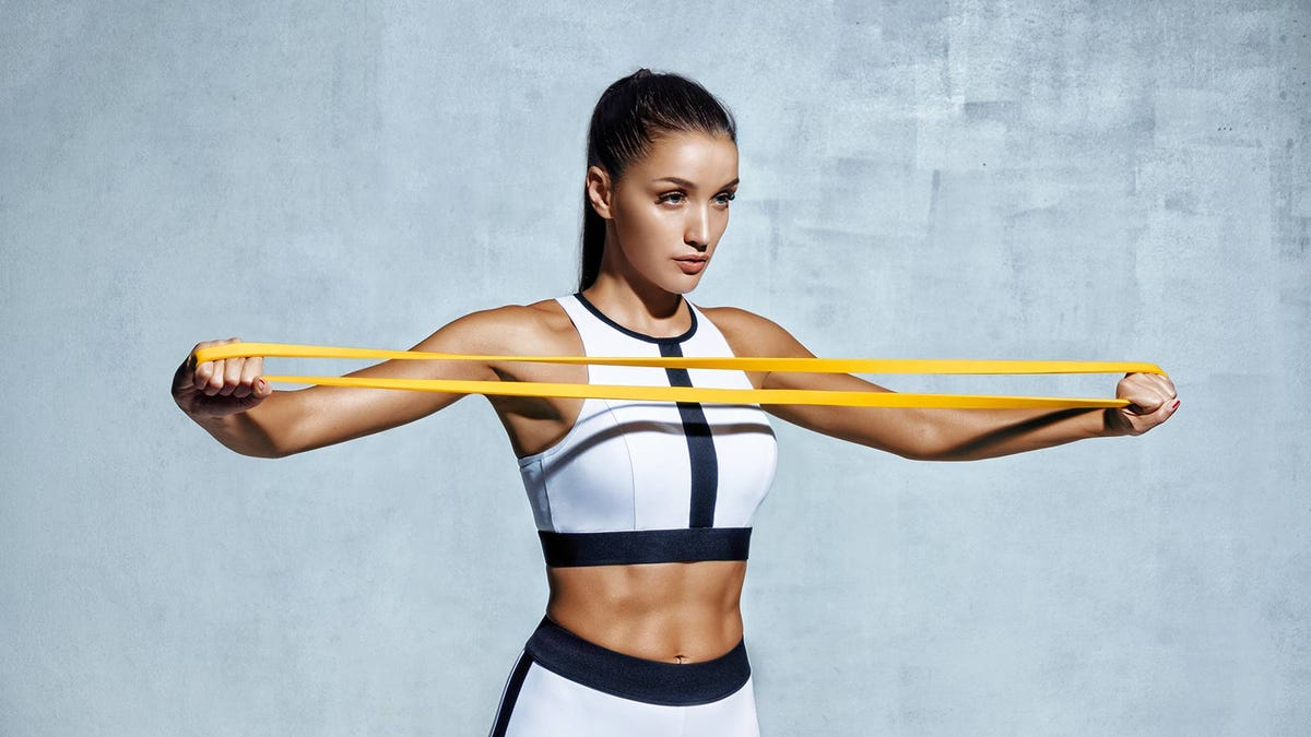 woman using a bright yellow resistance band to work her chest and shoulders