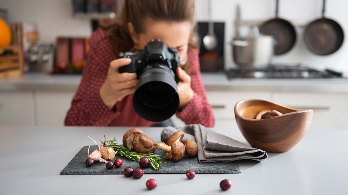 A woman taking pictures of food in her kitchen.