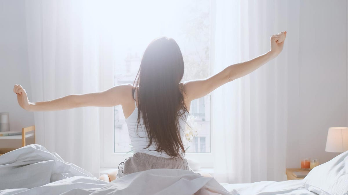 woman stretching in bed with the sun rising in the distance