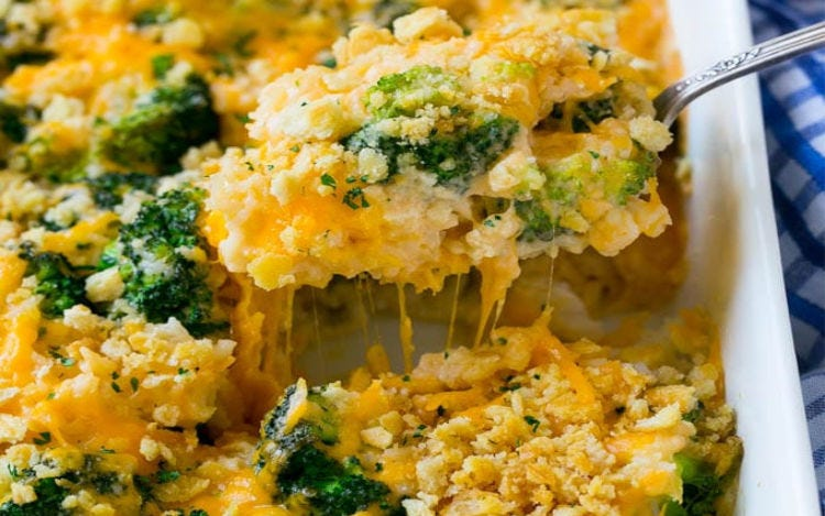 A casserole dish filled with broccoli and cheese casserole, with a scoop being taken out.