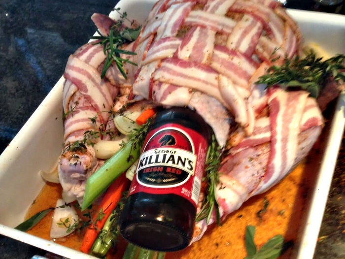 A raw turkey in a roasting pan covered with bacon, fresh herbs, and stuffed with aromatics and a beer bottle.