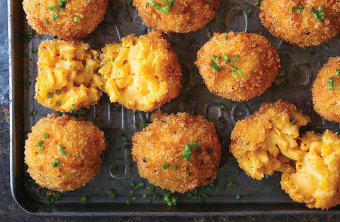 A few fried mac and cheese balls on a cookie sheet