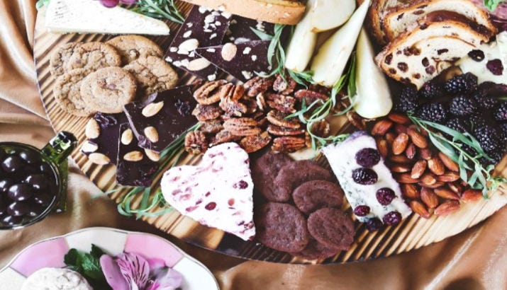 A dessert board filled with fresh berries, biscotti, chocolate and cheese.