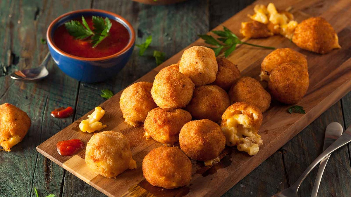 fried mac and cheese balls on a cutting board with sauce