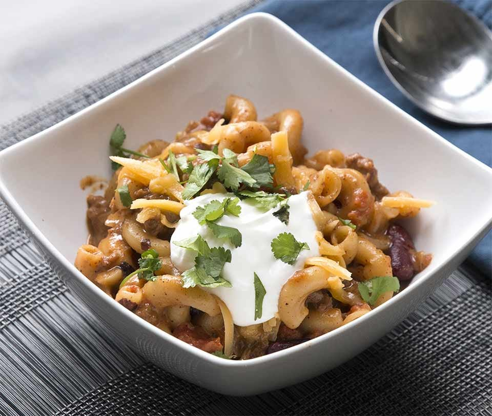chili Mac and cheese in a bowl with sour cream and garnish