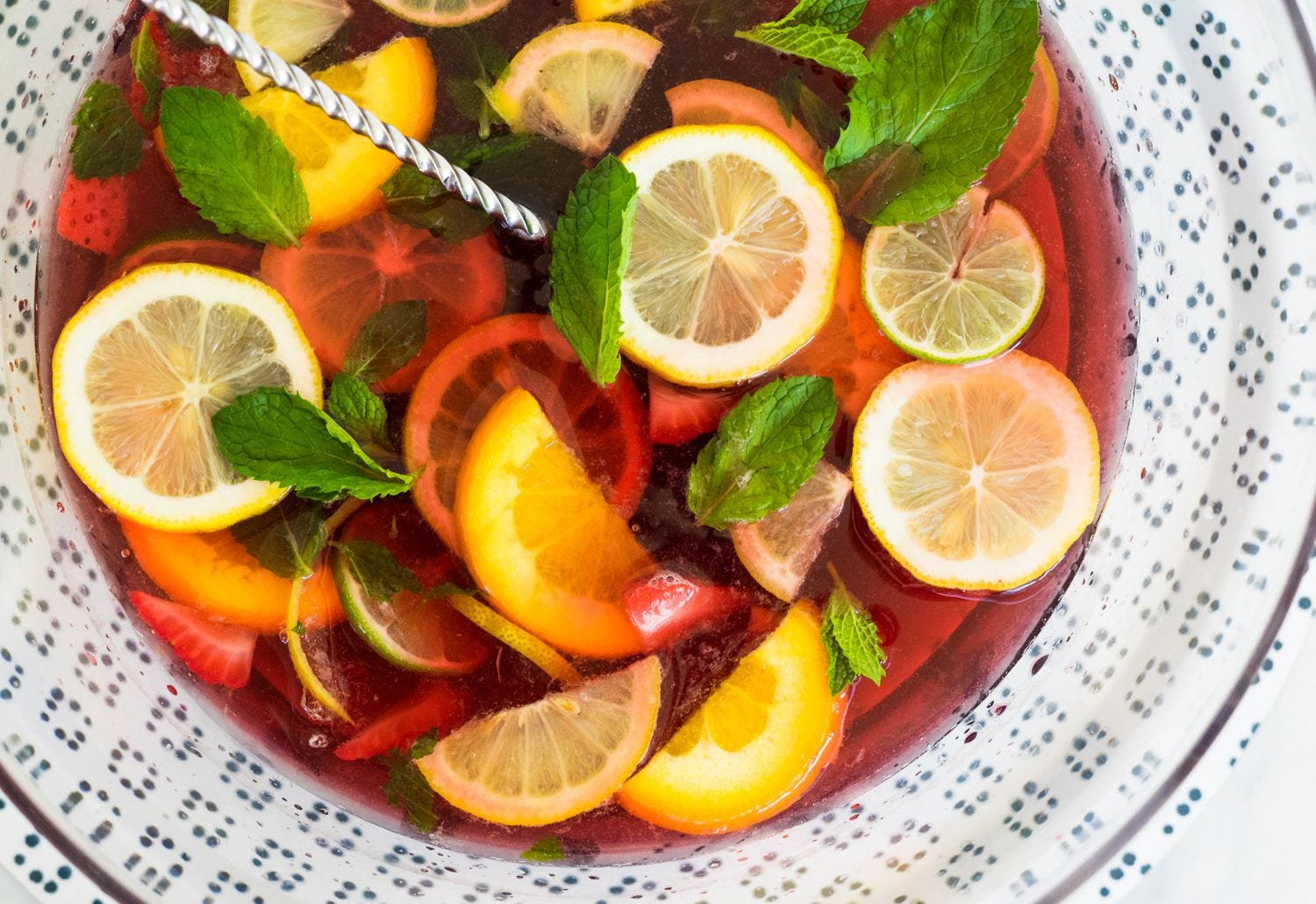 a yummy citrus holiday punch in a large bowl with mint leaves