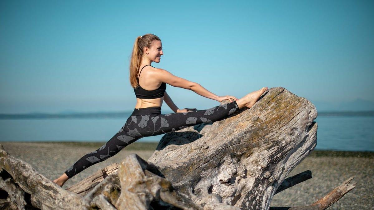 woman doing a split on the beach