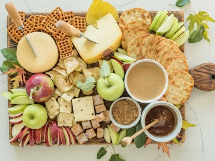 A gorgeous platter filled with autumn fruits, cheese and caramel dip.